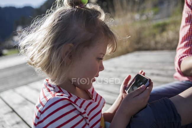 Chica sosteniendo el teléfono celular de madre en un embarcadero - foto de stock