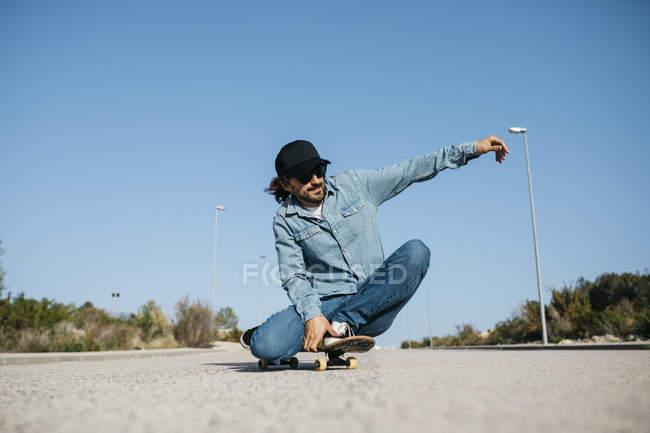 Homme à la mode dans le denim et la planche à roulettes de chapeau sur la rue — Photo de stock