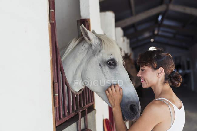 Усміхнена жінка гладить кінь у стабільній — стокове фото