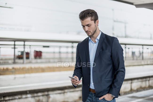 Businessman using cell phone at the platform — Stock Photo
