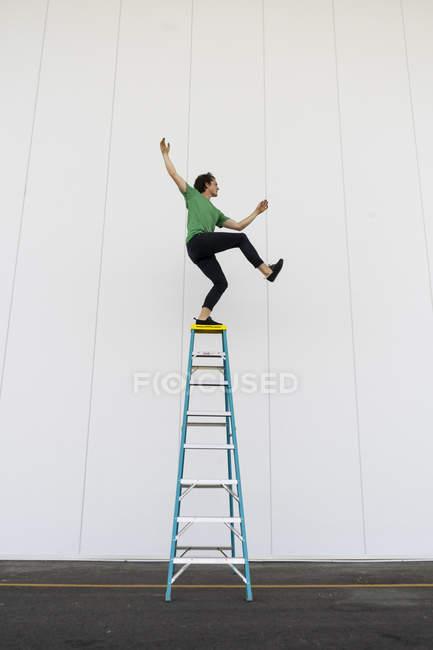Балансировка акробата на лестнице — стоковое фото