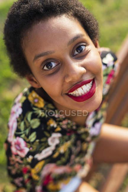 Портрет улыбающейся молодой женщины, сидящей на скамейке в парке — стоковое фото