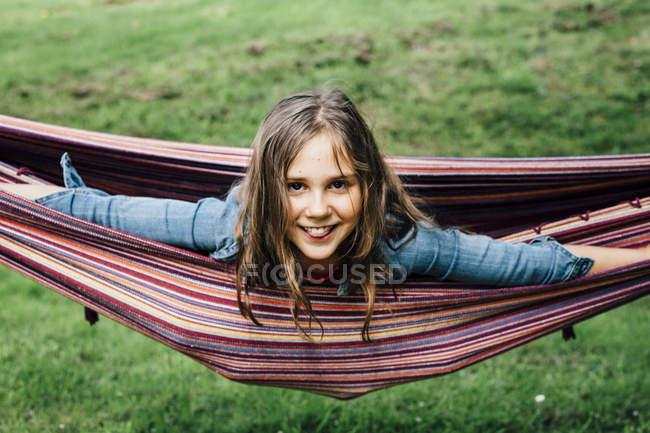 Ritratto di ragazza sorridente sdraiata sull'amaca che sporge la lingua — Foto stock