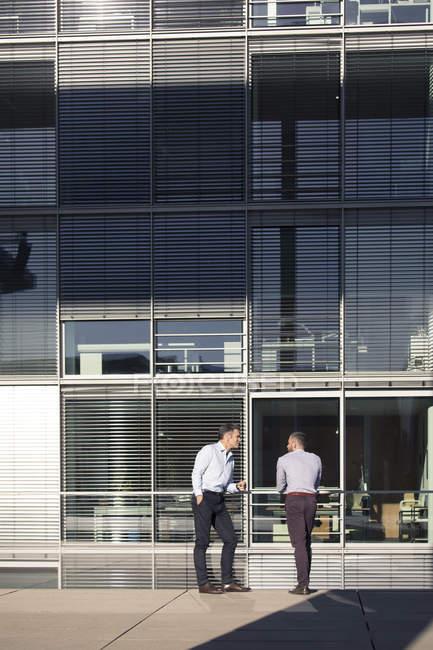 Dos hombres de negocios hablando exterior edificio de oficinas - foto de stock