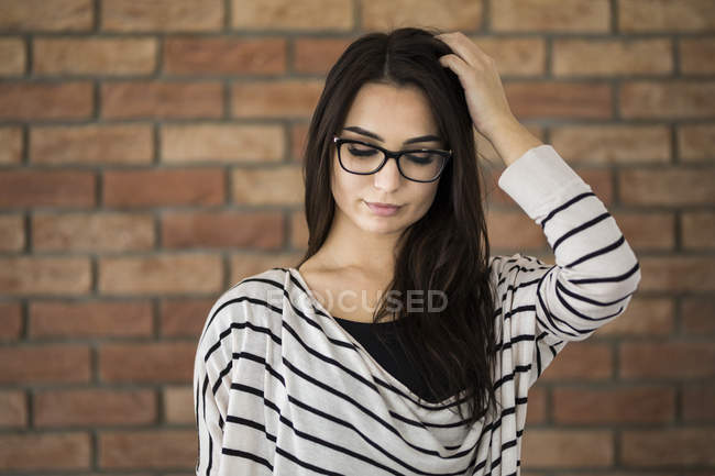 Portrait of young woman with long brown hair wearing glasses — Stock Photo