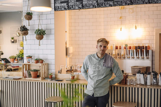 Young man working in startup cafe, portrait — Stock Photo