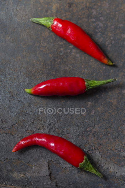 Three Red Chilli Peppers on rusty metal — Stock Photo