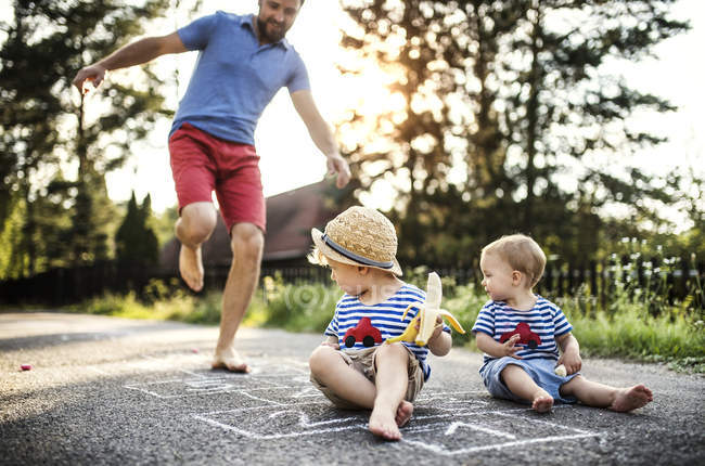 Man playing hopscotch while his little children watching him — Stock Photo