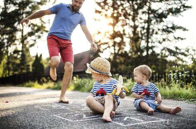 Mann spielt Hopscotch, während seine kleinen Kinder ihn beobachten — Stockfoto