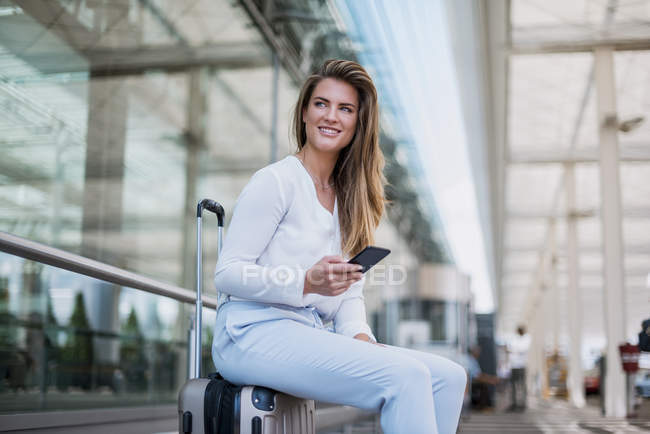 Smiling young businesswoman sitting on luggage with cell phone looking around — Stock Photo