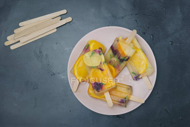 Homemade orange and lemon popsicles with edible flowers on plate — Stock Photo