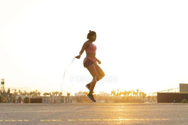 Испания, Барселона, молодая чернокожая женщина прыгает с рассветом — стоковое фото