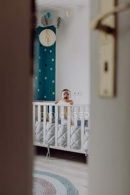 Baby boy standing in cot with open mouth — Fotografia de Stock