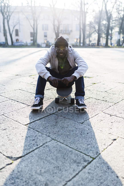 Young man with skateboard sitting on urban square — Foto stock