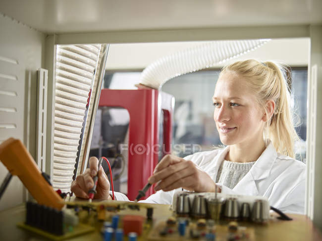 Female technician maintaining CNC machine — Stock Photo