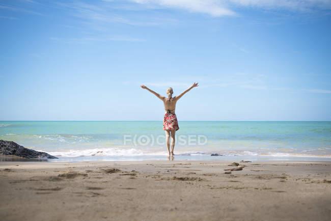 Таиланд, Као Лак, вид сзади счастливой женщины, стоящей на пляже на берегу моря — стоковое фото