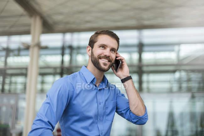 Улыбающийся молодой бизнесмен на улице — стоковое фото