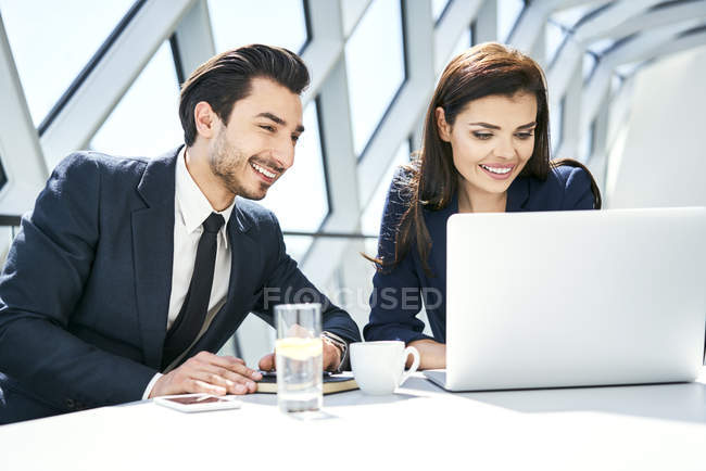 Smiling businesswoman and businessman using laptop at desk in modern office — Stock Photo