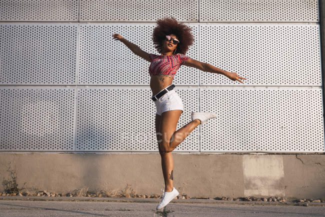 Fashionable young woman jumping in air against building wall