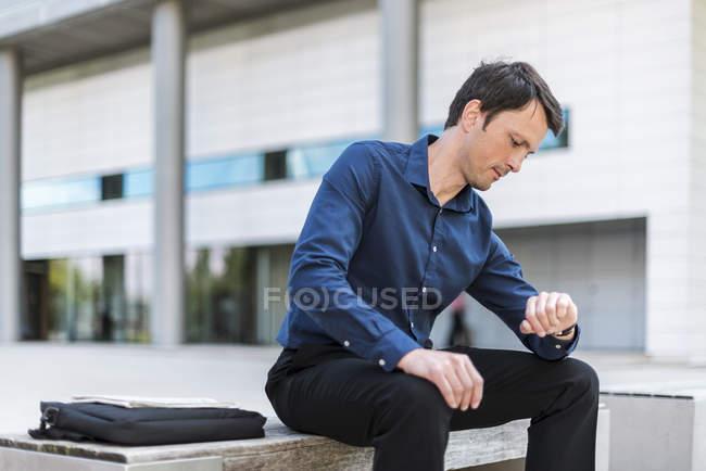 Uomo d'affari seduto all'aperto a controllare l'ora — Foto stock