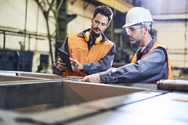 Men wearing protective workwear working with tablet in factory — Stock Photo