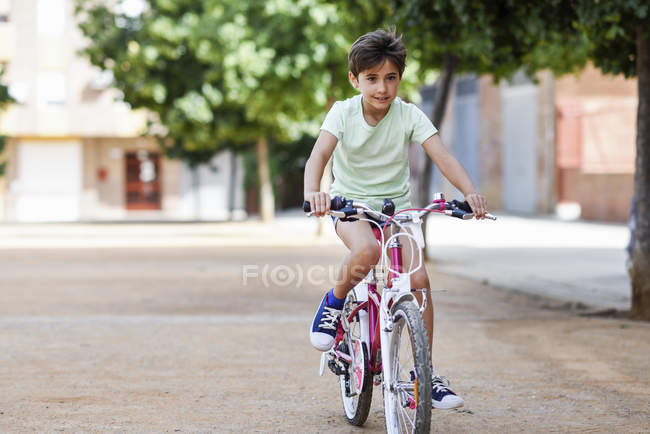 Portrait of little girl riding bicycle on street — Stock Photo