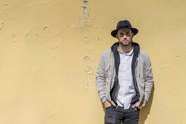 Bearded man wearing black hat, leaning on wall — Stock Photo