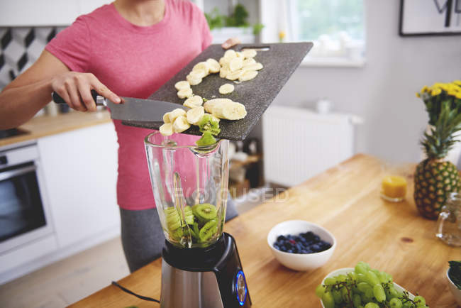 Молодая женщина готовит смузи на кухне, добавляя фрукты в блендер — стоковое фото
