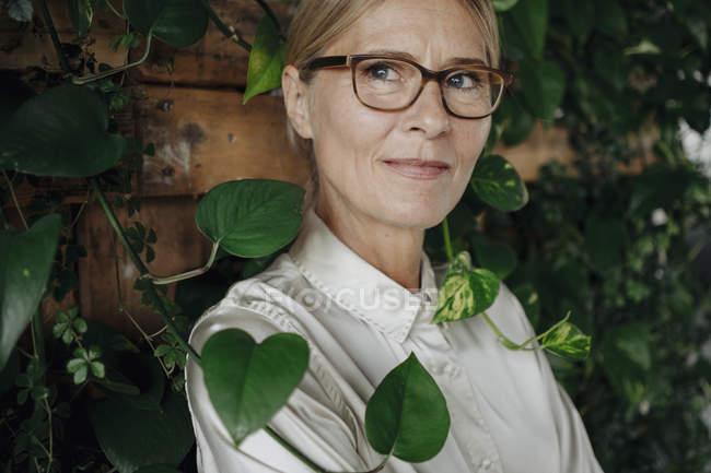 Ritratto di donna d'affari a parete con piante rampicanti — Foto stock