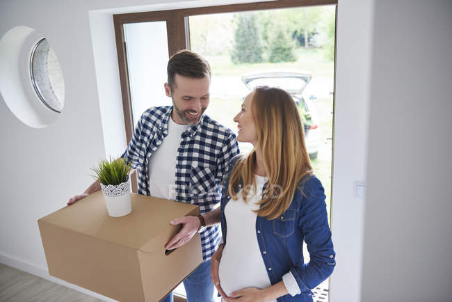 Happy man and pregnant woman moving into new flat carrying cardboard box — Stock Photo