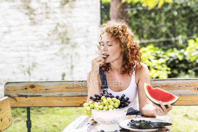 Рыжая молодая женщина ест виноград за деревенским столом летом — стоковое фото