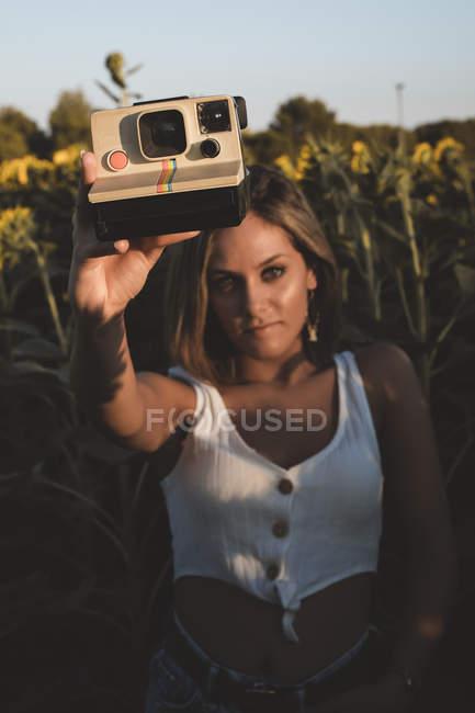 Молода жінка в області соняшнику тримає моментальну камеру — стокове фото