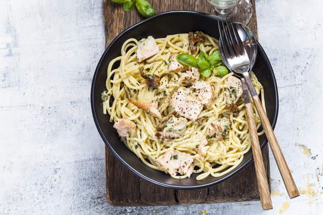 Spaghetti avec sauce crémeuse aux épinards, tomates séchées et saumon — Photo de stock