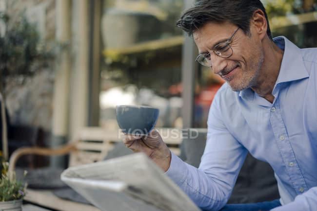 Uomo d'affari maturo seduto in caffetteria, a bere caffè — Foto stock