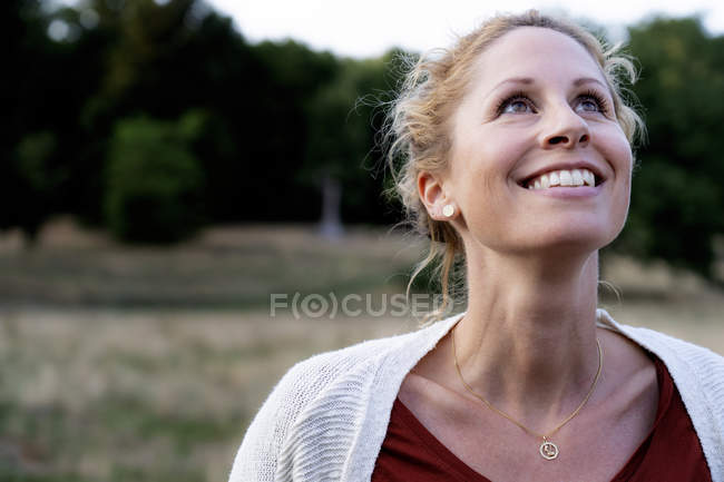 Portrait of smiling woman in nature looking up — Stock Photo