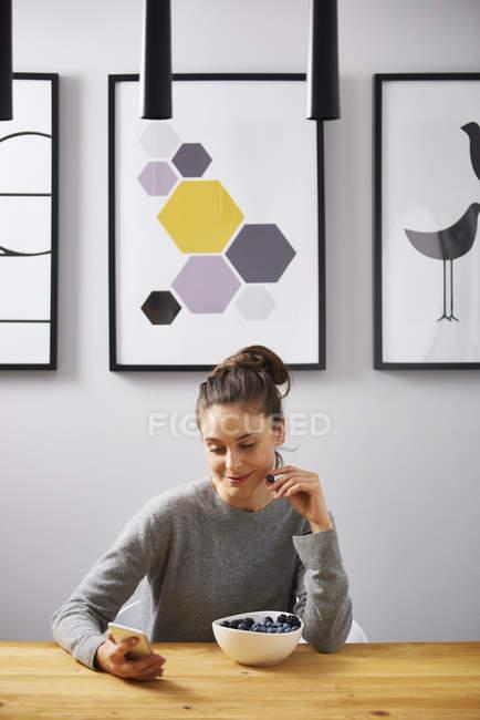 Giovane donna seduta a tavola a casa, a leggere messaggi di testo — Foto stock