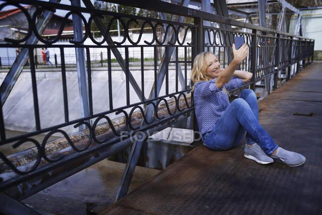 Blondine sitzt auf Brücke und macht Selfie mit Handy — Stockfoto