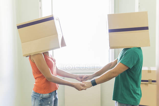 Couple with heads in cardboard boxes holding hands — Stock Photo