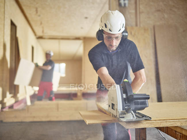 Worker with helmet sawing wood with circular saw — Stock Photo