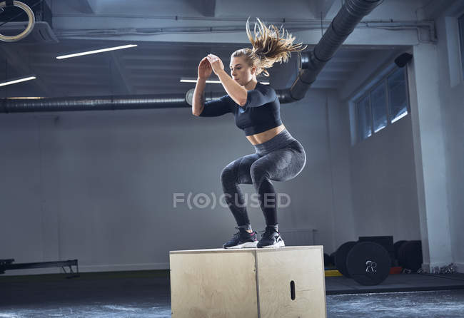 Athletic woman doing box jump exercise at gym — Stock Photo