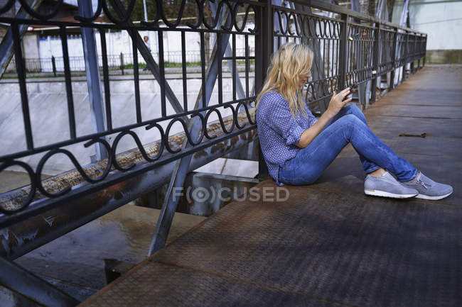 Blonde Frau auf Brücke surft mobil — Stockfoto