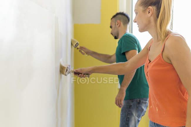 Парочка покраски стены в новом доме — стоковое фото
