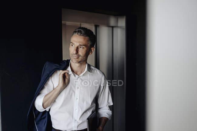 Бизнесмен в офисе держит ноутбук — стоковое фото