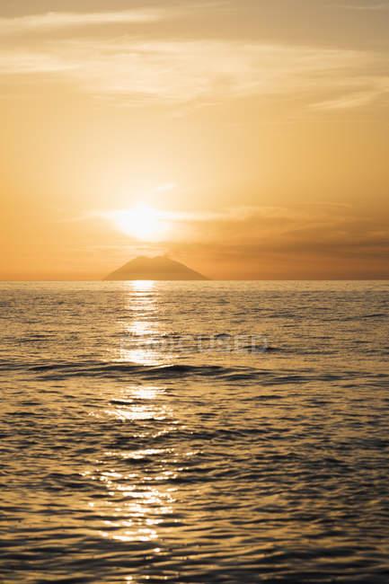 Italien, Kalabrien, Tropen, Tyrrhenisches Meer, Blick auf Vulkaninsel Stromboli gegen die Sonne — Stockfoto