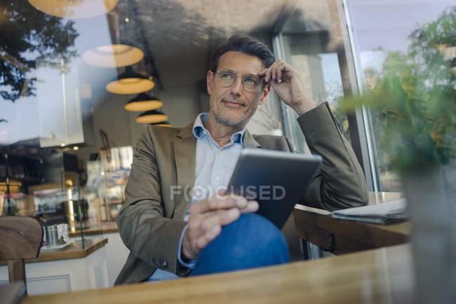 Geschäftsmann sitzt mit digitalem Tablet im Coffeeshop — Stockfoto