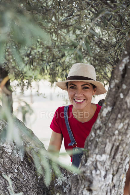 Portrait of smiling woman behind olive tree — Stock Photo