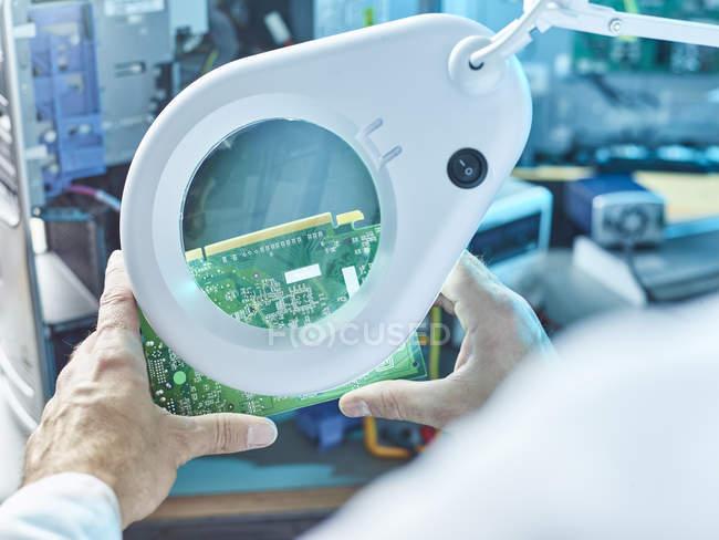 Técnico que verific a placa de circuito com Magnifier — Fotografia de Stock