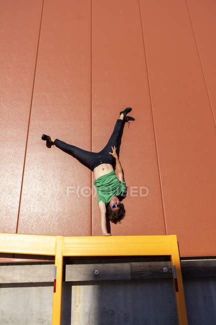 Acrobat выполняет однорукую стойку на руке на желтой раме — стоковое фото