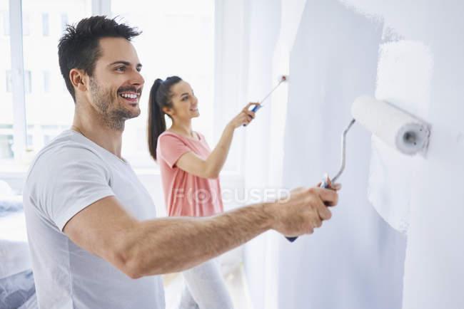 Счастливая пара вместе рисует стены в квартире — стоковое фото