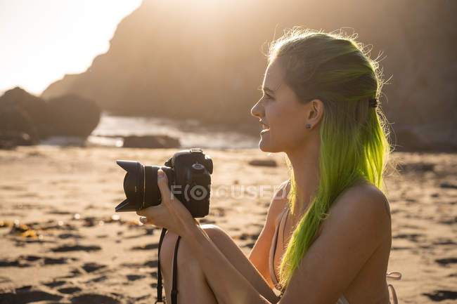 USA, California, West Coast, young woman with dyed green hair and camera sitting on the beach — Stock Photo
